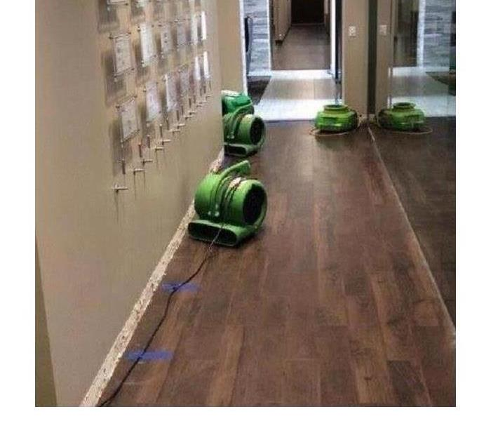 living area with wood floors being dried out by SERVPRO machines