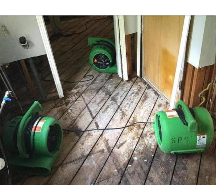 old wood floor being dried out by several green SERVPRO machines